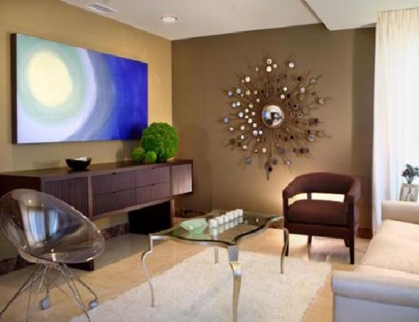 Contemporary style living room area with large sunburst mirror decor on the beige wall, large blue artwork above the wood table, ghost chair, rug on a hardwood floor, and glass coffee table.