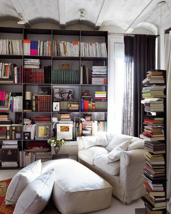 Overstuffed sofa and lots of books-shelf with a reading nook