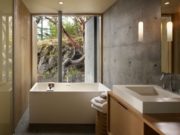 bathroom interior design with concrete walls and square shaped bathtub with glass window transparent