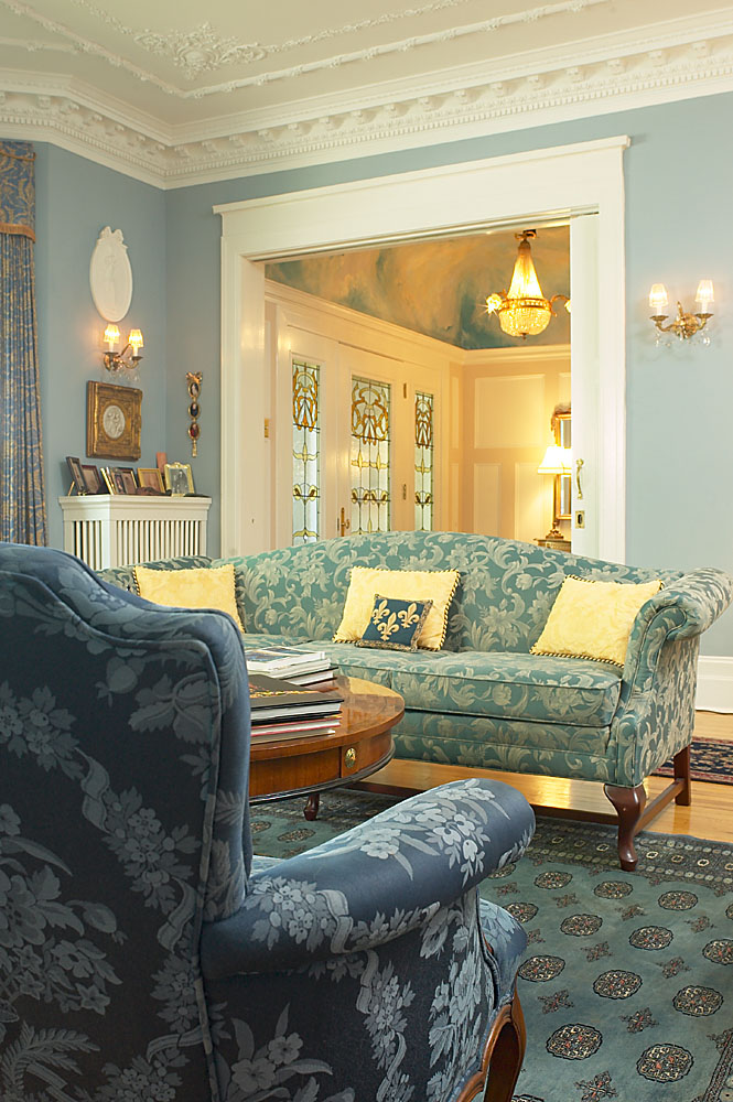 The sofa, crown molding, carpet, and wall sconces create a traditional style